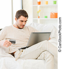 young man with laptop and credit card at home - picture of...