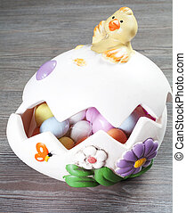 colorful eggs in the egg shaped with chick on the wood table