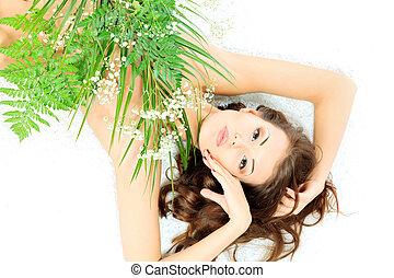 eternal youth - Beautiful young woman lying among fresh...