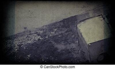 Hard worker on steamroller flattens asphalt. Vintage 8mm...