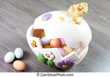 colorfull eggs in the egg shaped eith chick on the wood...