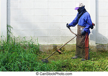 Mowing - Worker mowing weed near the fence with mowing...