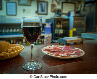 Glass of wine and jamon plate