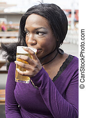 Young African American Woman Drinks Pint of Pale Ale - Young...