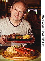 aged man eating grilled sausages - Happy aged man eating...