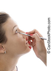 model getting eye makeup on an isolated background