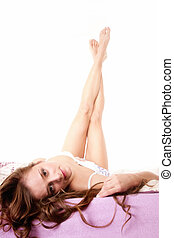 woman lying in bed her feet crossed in the air
