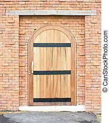 Closed wooden door with brick wall.