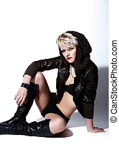 High fashion look.glamor portrait of beautiful sexy stylish Caucasian young  blond woman  model in black cloth with bright makeup with short hair sitting on white background
