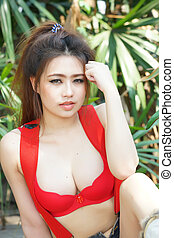 Young beautiful Asian woman in red lingerie with short pants...