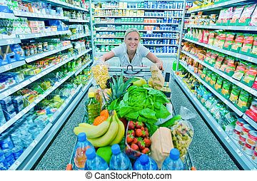 woman with shopping cart in the supermarket - a woman when...