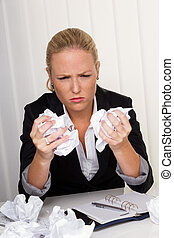 woman in office with crumpled paper - a woman in the office...