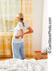 woman with back pain - a woman has the morning after waking...