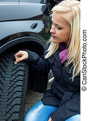 woman measures tire tread of a car tire