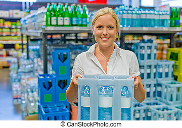 woman buys bottled water at the grocery store - a young...