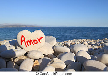 ldquo;Amorrdquo; written on heart shaped stone on the beach...