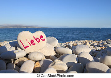 """Liebe"" written on heart shaped stone on the beach"