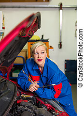 woman as a mechanic in car workshop