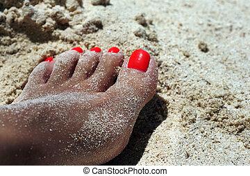Sunburnt female leg on damp sand