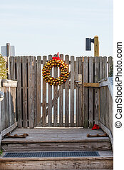 Gold Christmas Wreath on Gate to Beach - A gold wreath at...