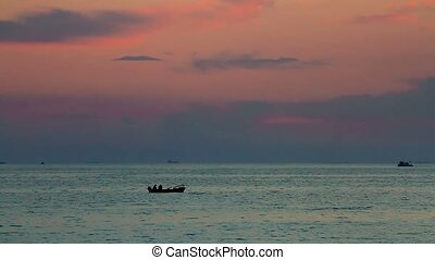 Sea at sunset   - Calm sea with a rowing boat at sunset.