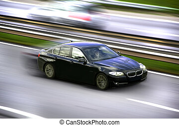 Car panning - A luxurious car speeding.