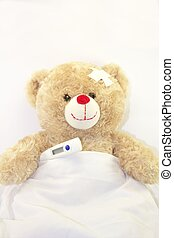 Ill teddy bear with a thermometer on white background