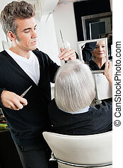 Hairstylist Cutting Hair At Salon - Senior client holding...
