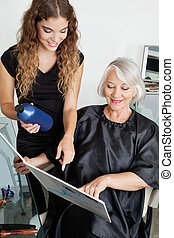 Client And Hairdresser Choosing Hair Color - Senior female...