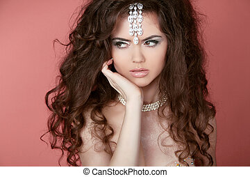 Beautiful brunette woman with long curly hair. Jewelry and...
