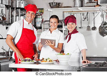 Happy Chefs Using Tablet Computer In Kitchen - Portrait of...