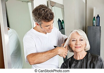 Client Getting Haircut By Hairstylist - Senior client...