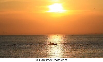 Sea at sunset - Calm sea with a rowing boat at sunset