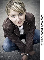 Blonde girl smiling - Girl with blonde fringe squatting down...