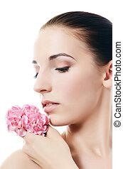 The beautiful woman holds a flower of a carnation at the face