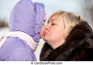Caucasian mother kissing her daughter. People in winter clothing