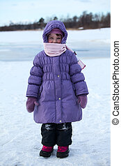 Wrapped in warm clothing little child standing outdoor in...