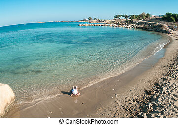 Wide angle view of small Caucasian child playing on sandy beach of Mediterranean sea, Cyprus
