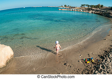 Little Caucasian child playing on sandy beach of Mediterranean sea, Cyprus. Wide angle view