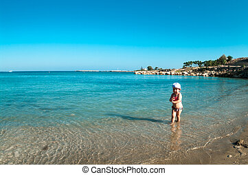 Little Caucasian child playing on sandy beach of Mediterranean sea, Cyprus