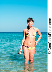 Portrait of a happy young woman in bikini standing in sea. Copyspace