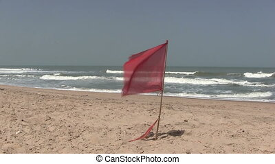 Red warning flag flying on a deserted beach in The Gambia,...