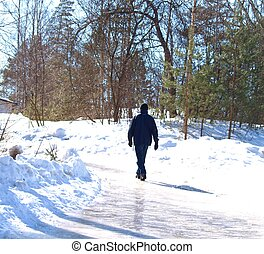 Person walking up a icy road at winter, strong sunlight