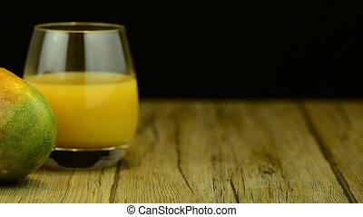 Apple mango and juice sliding on wood table top on black...