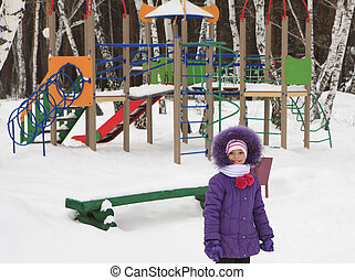 Little girl on the background of children's playground in the winter forest.