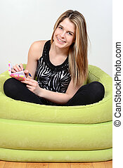 teen girl writing in her journal sitting in green chair
