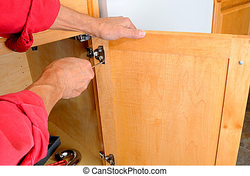 Attaching Hinge to Cabinet - Closeup of a installers hands...