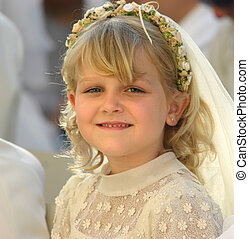 First holy communion - A blond girl smiling at the camera,...