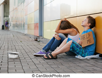 homelessness - Homeless teenage boy and girl begging in...