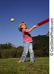 Girl playing rounders - A young girl batting a ball, playing...